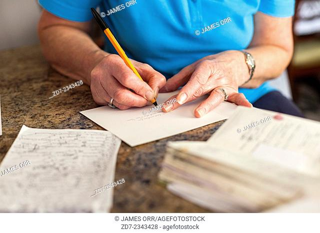 Middle aged woman writing Christmas cards