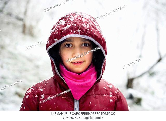Portrait of little girl in the woods while snowing