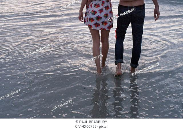 Young couple walking in ocean surf