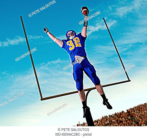 American footballer jumping to catch ball in front of goal