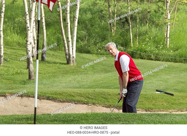 middle-aged golfer hitting golf ball out of sand trap