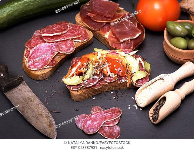 sandwiches with pieces of sausage salami and a hamon on a black background, seasoned with spices