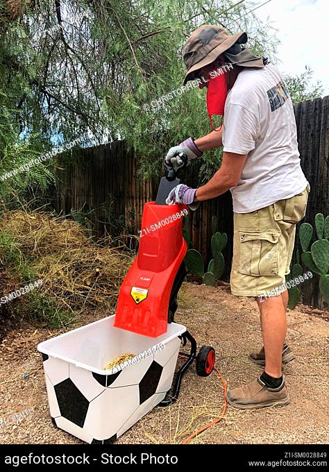Adult male wearing thick protective gloves feeds garden sticks and small branches into an electric wood chipper