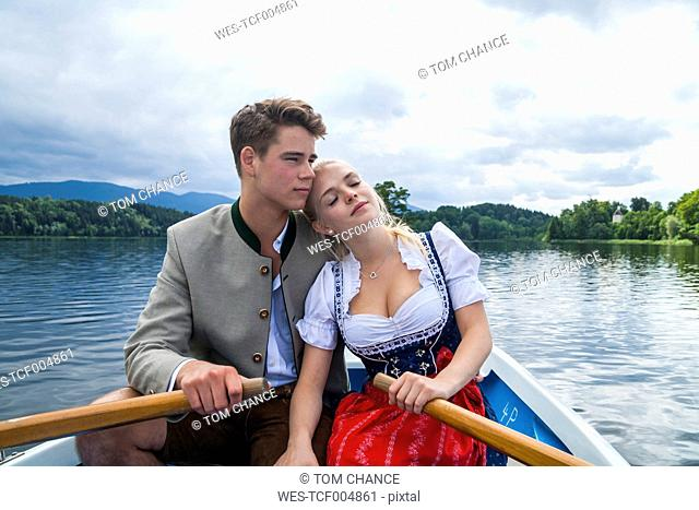 Germany, Bavaria, young couple in love wearing traditional clothes sitting in a rowing boat on Staffelsee
