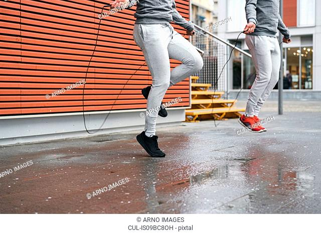 Male adult twins training, skipping with ropes on sidewalk