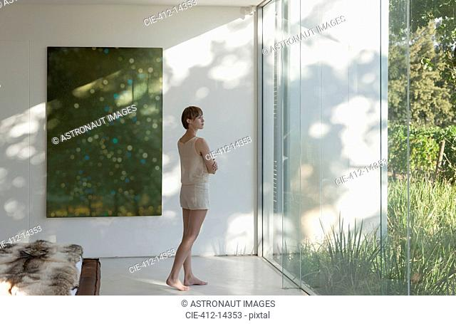 Woman standing at window in modern bedroom