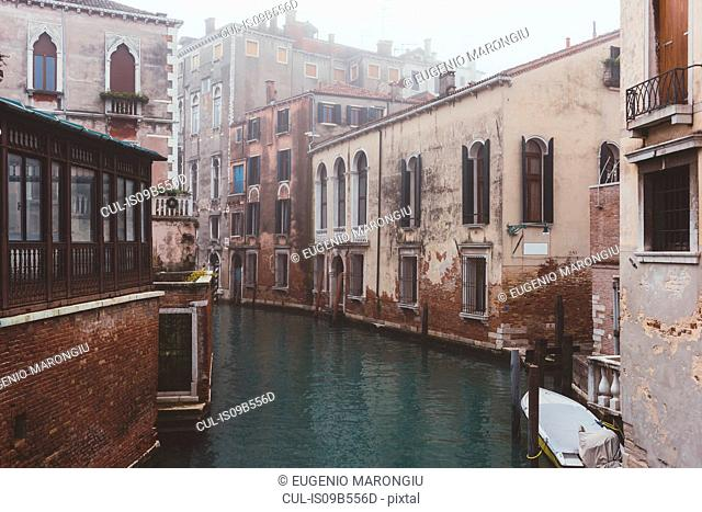 View of misty canal and old buildings, Venice, Italy