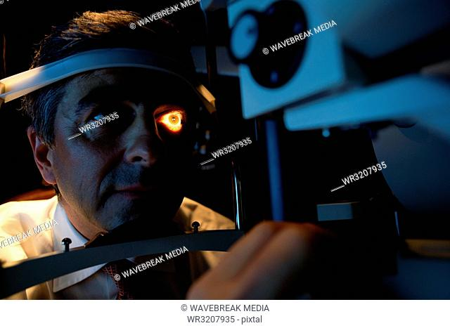 Optometrist examining patient eyes with slit lamp