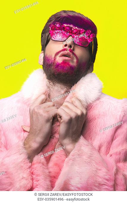 Portrait of glamour man with red beard. Guy in a pink fur coat and funny sunglasses