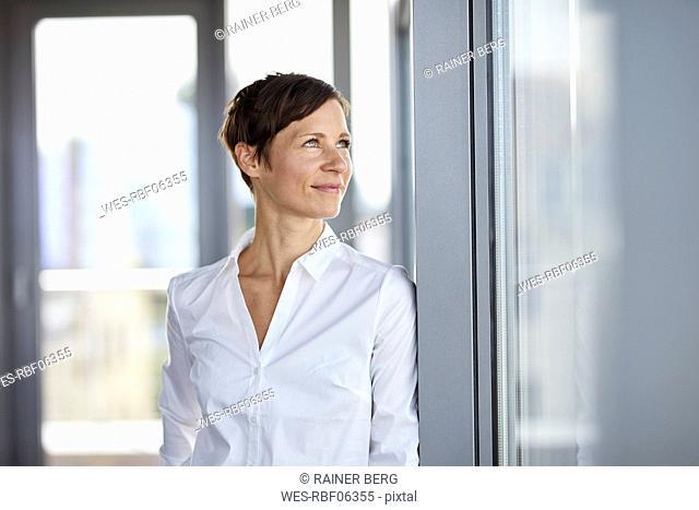 Smiling businesswoman in office looking sideways