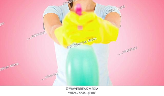 Female cleaner holding a cleaning spray bottle against pink background