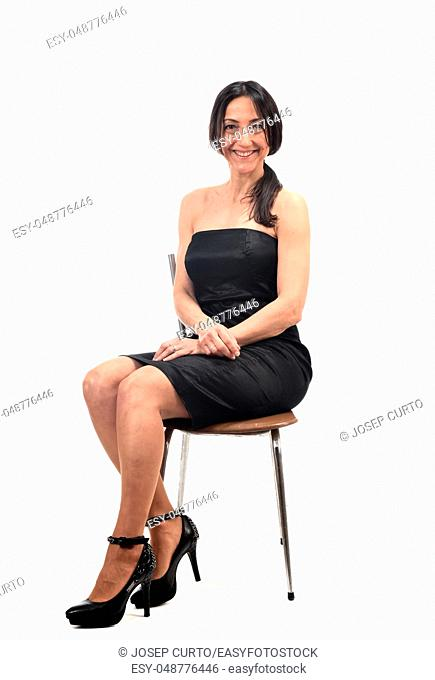 woman with off shoulder dress sitting on a chair isolated on white