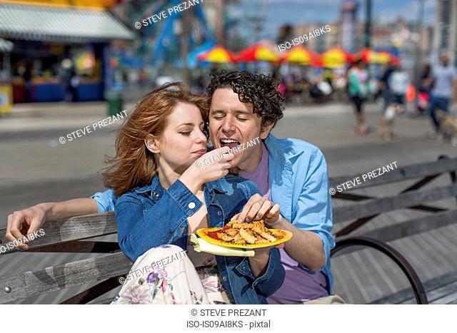 Romantic couple eating chips at amusement park