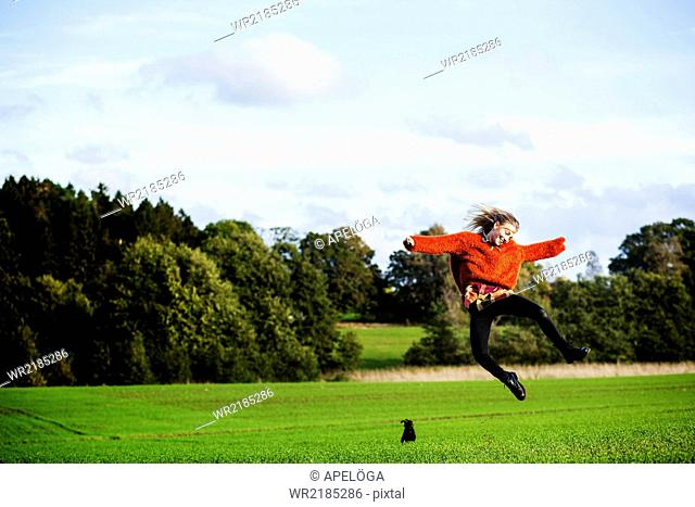 Happy young woman jumping on field