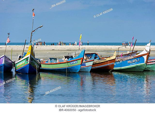 Brightly painted fishing boats and people on the beach, near Alappuzha, Kerala, India