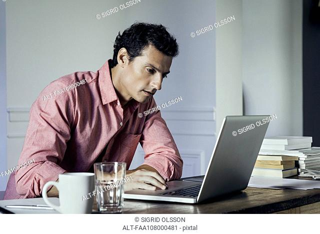 Man working on laptop computer at home