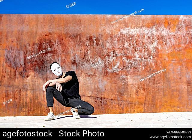 Man wearing face mask crouching against wall during sunny day