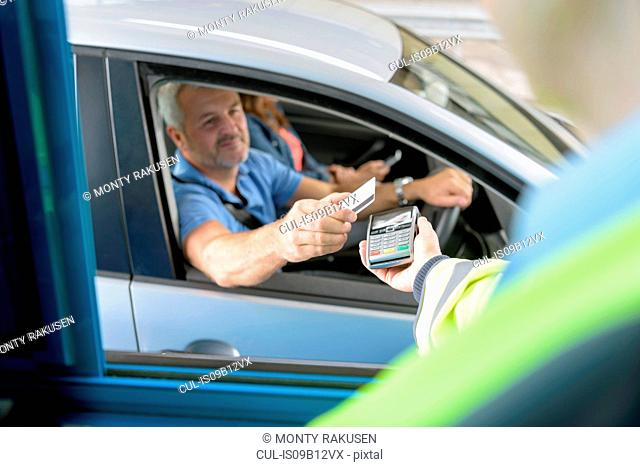 Driver in car paying toll booth at bridge using contactless card payment technology