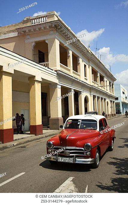 Old American car used as taxi in front of the colonial buildings in the city center, Cienfuegos, Cienfuegos Province, Cuba, Central America