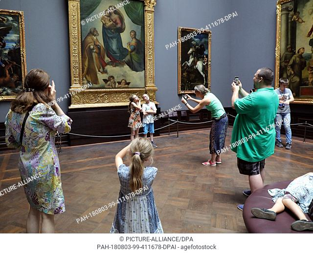 02 August 2018, Germany, Dresden: A family from the Czech Republic photographs their children in the exhibition Old Masters in the Zwinger in Dresden