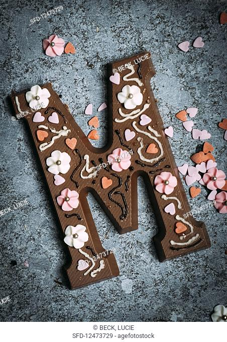A chocolate letter M decorated with sugar flowers and hearts