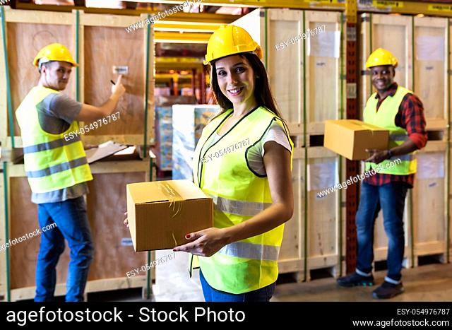 Portrait of caucasian white woman warehouse worker hold parcel box with her colleague working about stock in warehouse distribution center environment