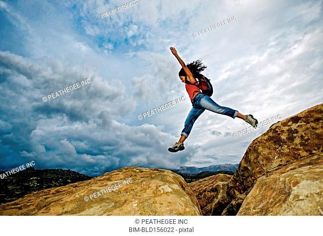 Hispanic woman jumping crevasse on rock formation