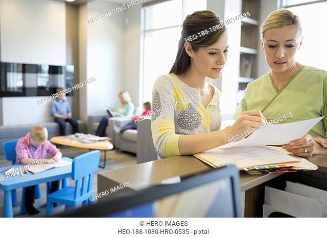 Dental assistant and receptionist reviewing medical records