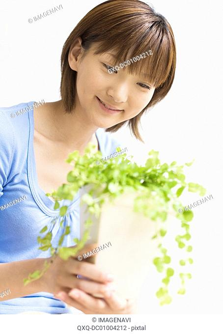 A woman looking at foliage plant
