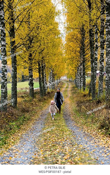 Finland, Kuopio, mother and little daughter strolling together in autumn