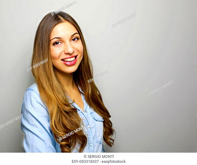 Confident business woman smiling at camera on gray background