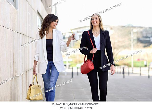 Two smiling businesswomen with handbags and coffee to go walking on pavement