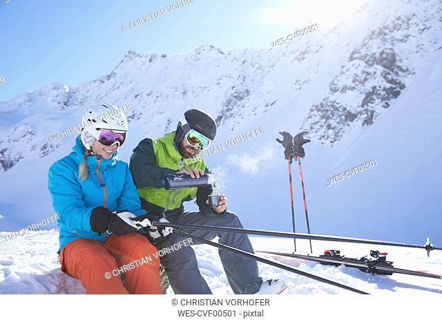 Austria, Tyrol, Kuehtai, two skiers in winter landscape having a break