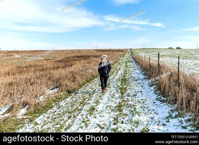 Woman walking in snowy field