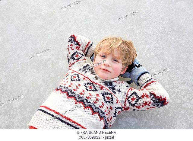 Overhead portrait of boy lying on frozen lake, Gavle, Sweden