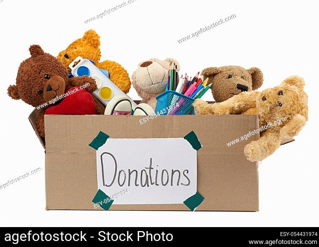 brown cardboard box filled with soft toys, school supplies isolated on white background, concept of charity and help to needy children