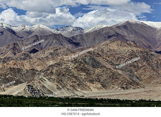 The breathtaking mountains tower above the Thiksey Gompa in Ladakh, India. The Gompa is located on top of a hill in the Indus Valley approximately 19 kilometers...