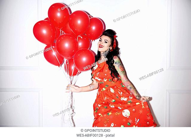 Portrait of tattooed woman with bunch of red balloons