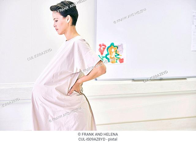 Side view of pregnant woman wearing hospital gown