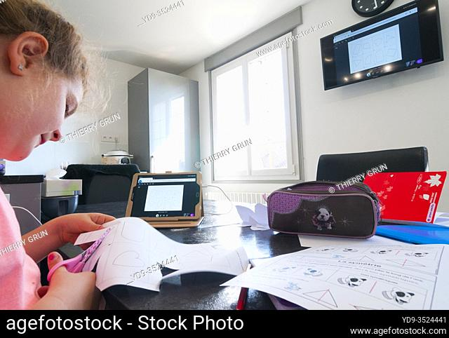France, Loiret (45), Covid-19 French lockdown on 04/27/2020, young girl of 7 years old in CE1 during virtual school class at home using tablet remote connection...