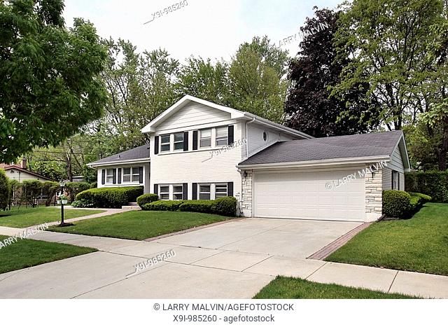White home in suburbs with side yard