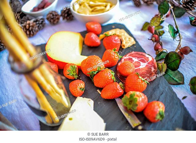 Detail of strawberries and cheese on picnic table