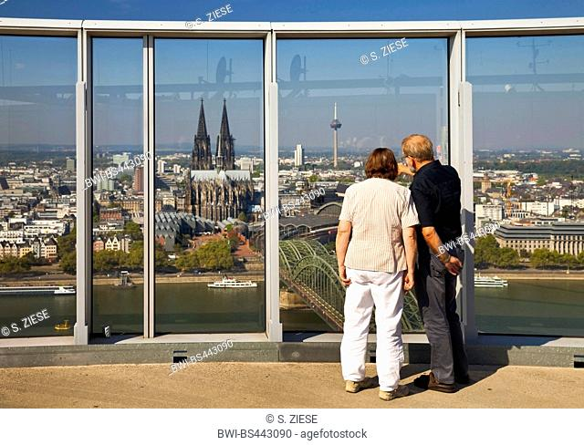 couple enjoying the view from KoelnTriangle oberservation deck to the city with Cologne Cathedral and Rhine, Germany, North Rhine-Westphalia, Cologne