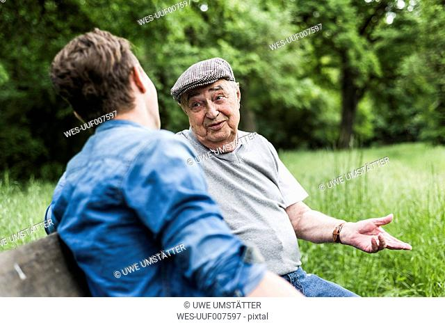 Portrait of senior man sitting on a bench talking to his grandson