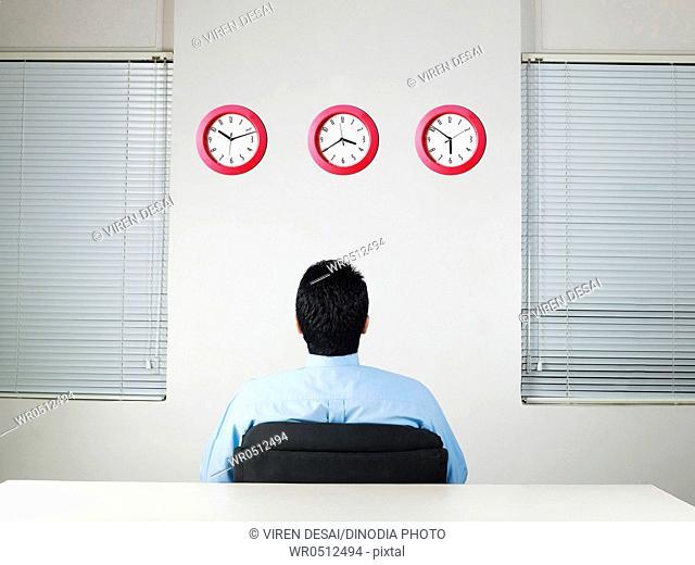 Executive looking at row of clocks MR 779K