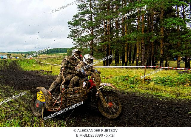 Caucasian racers on motorcycle with side car spraying dirt