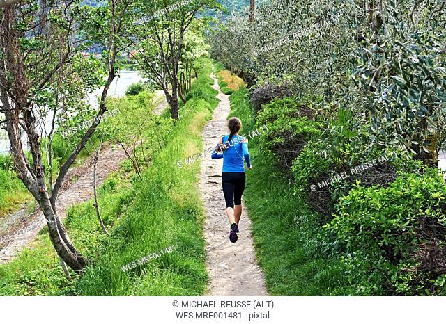 Italy, Trentino, woman running near Lake Garda