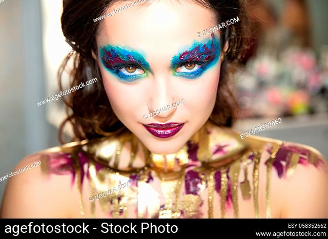 Pretty young brunette with creative make up and body painting