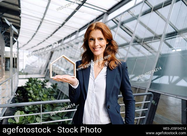Portait of a confident businesswoman holding a house model in office