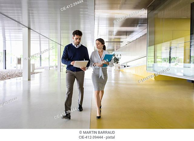 Businessman and businesswoman walking and discussing paperwork in modern office corridor